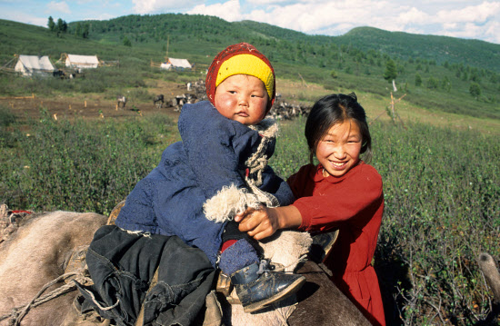 A young Tuvan woman holds a child sitting on a reindeer. Todzhu, Tuva, Siberia, Russia.