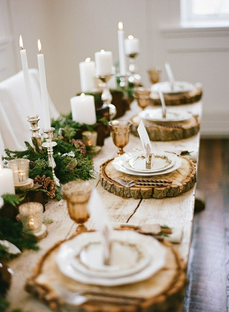 Christmas table with white candles and white dishes and wooden tray