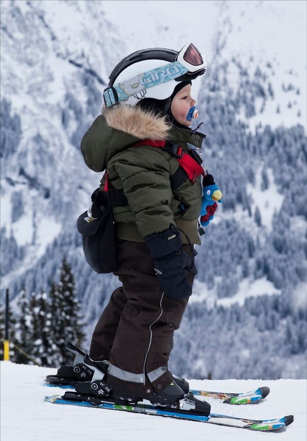 baby boy skiing with helmet and pacifier