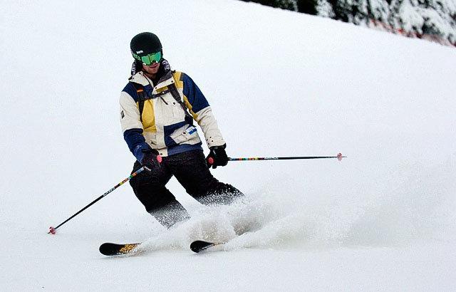 ski man with black ski pants and green mask