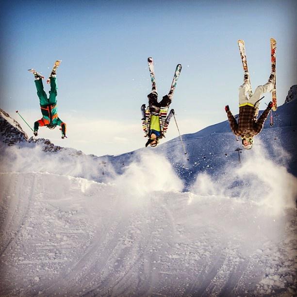 three skiers doing tricks