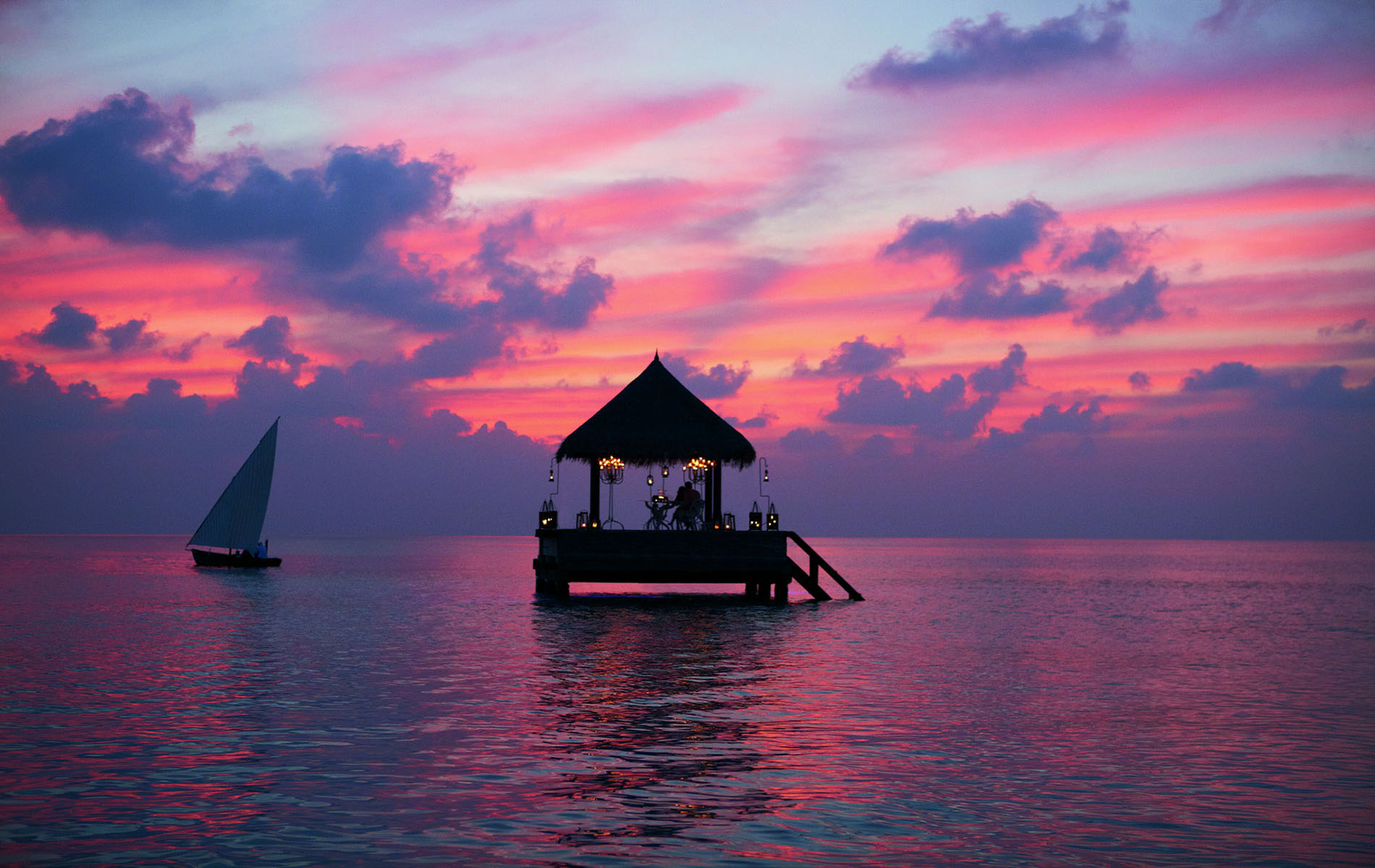 Maldives sunset with a boat and a house