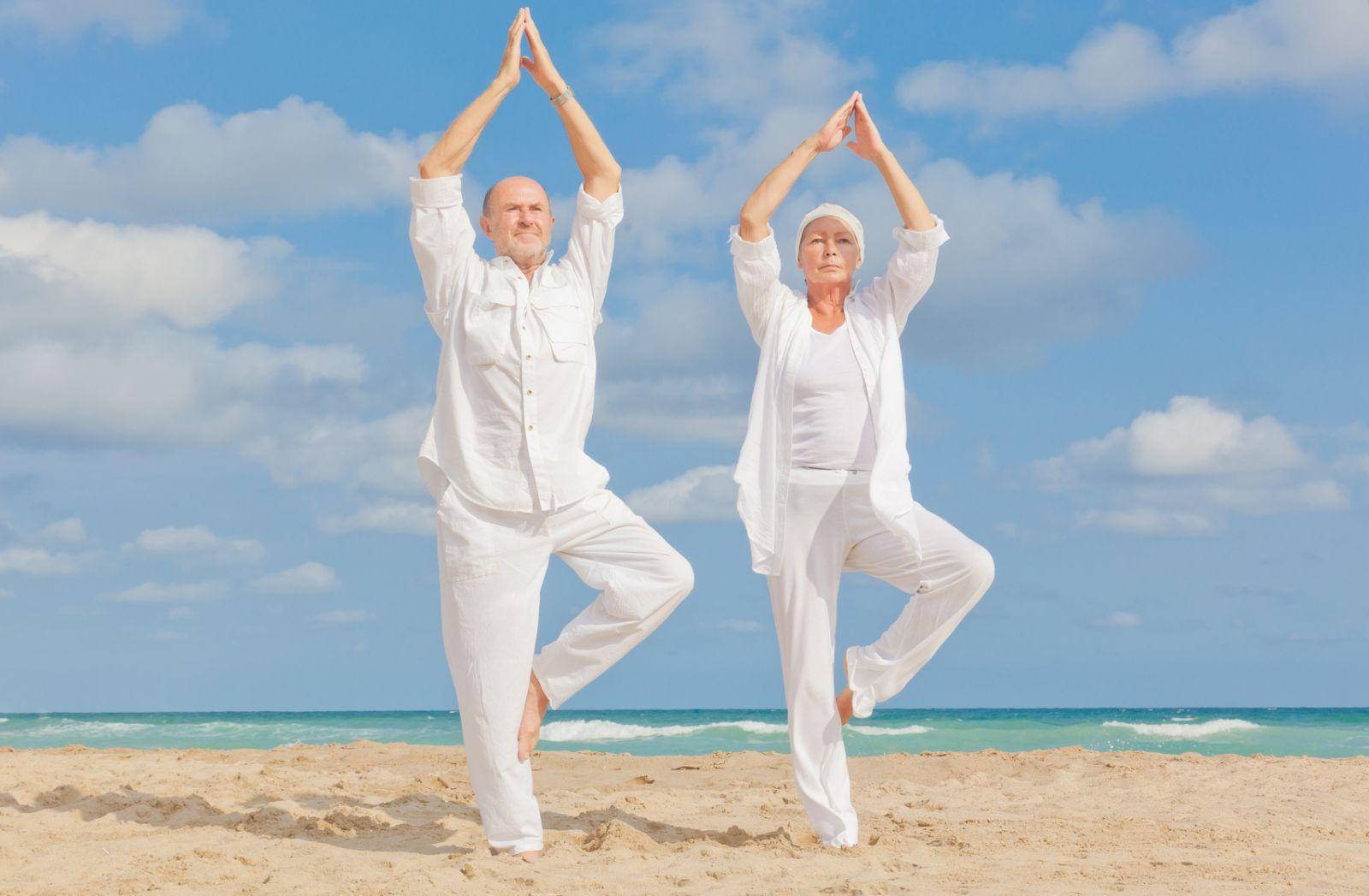 an old couple doing yoga on the beach