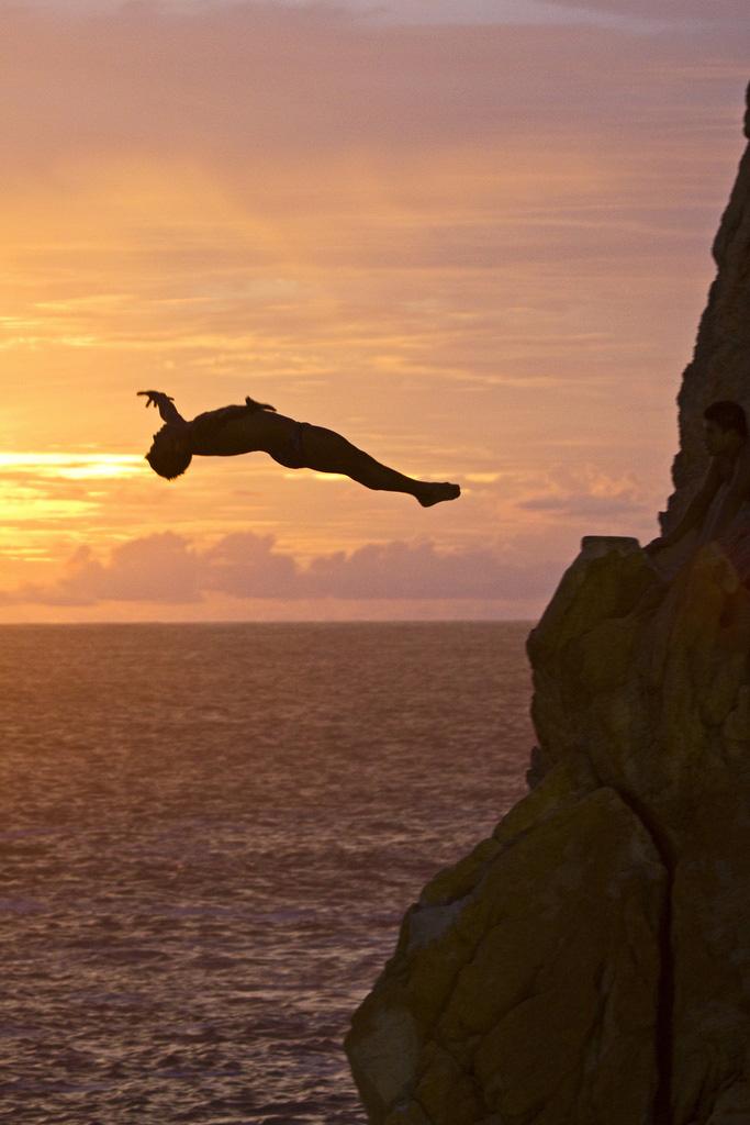 man jumping from La Quebrada rocks in mexico sunset
