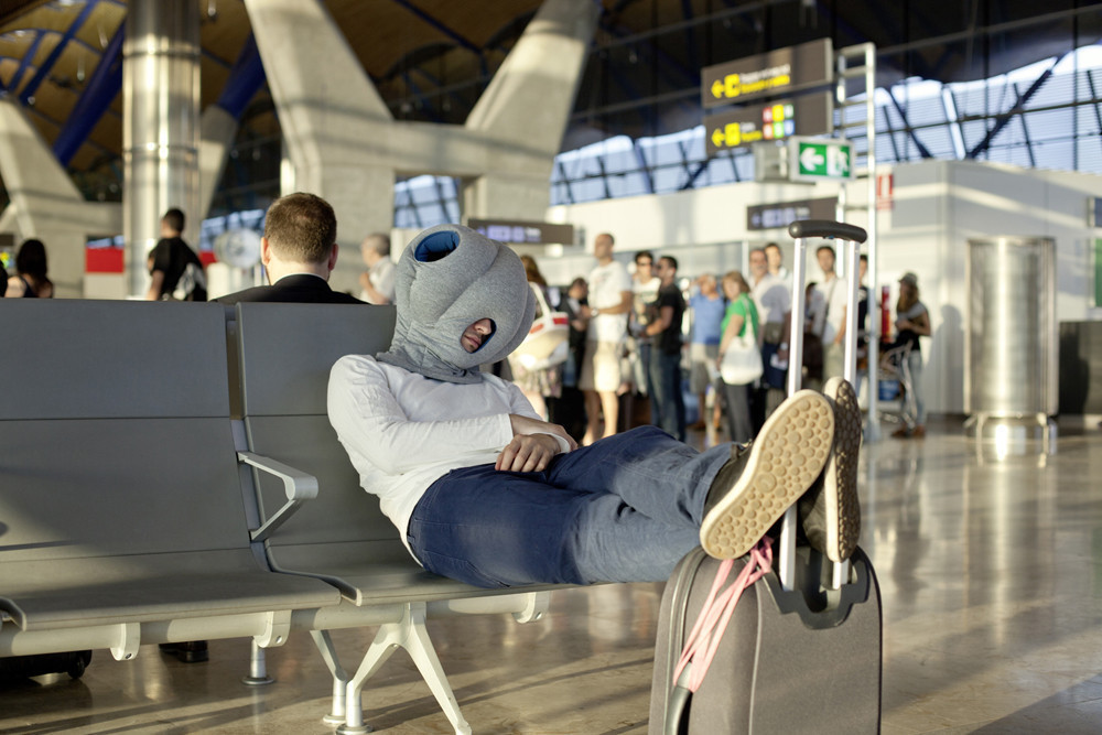 ostrich-pillow man sleeping on the airport