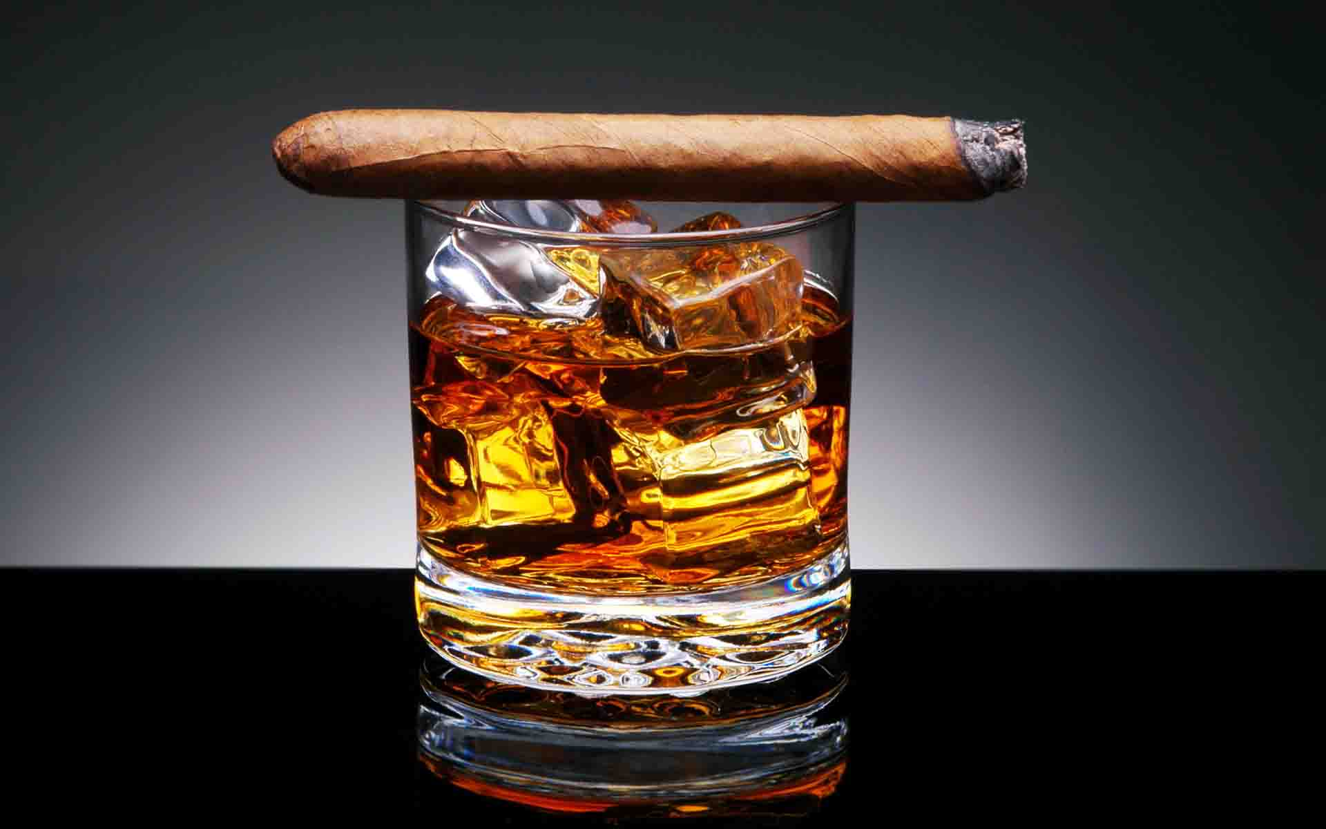 Whiskey in glass with cigar The whiskey was initially colorless