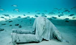 Underwater sculpture park, Grenada A man with head in the sand underwater