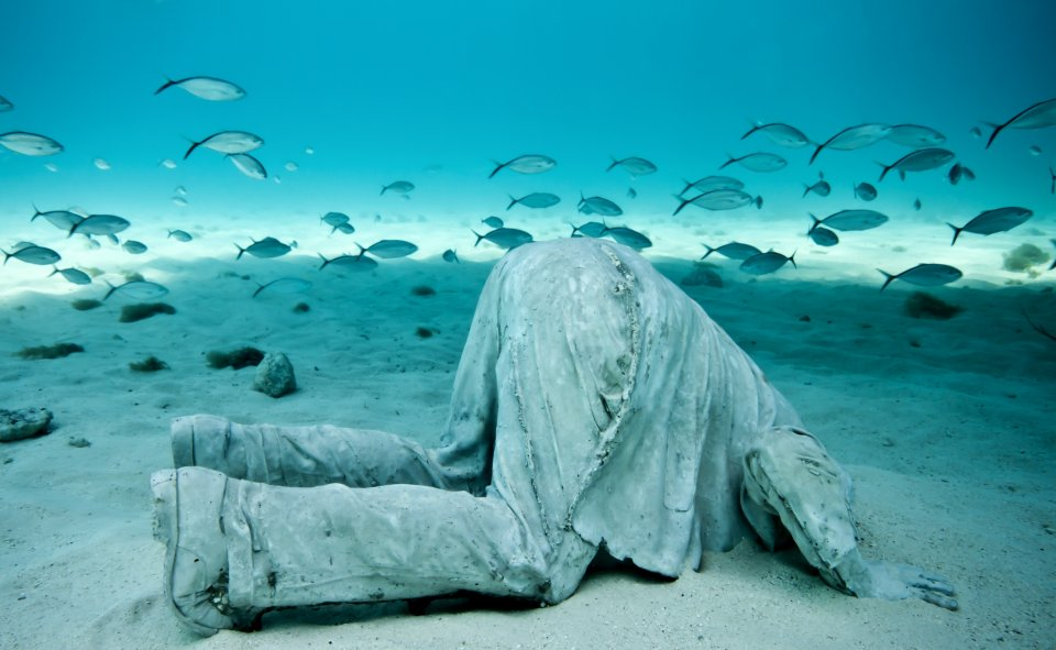 Underwater sculpture park, Grenada A man with head in the sand underwater