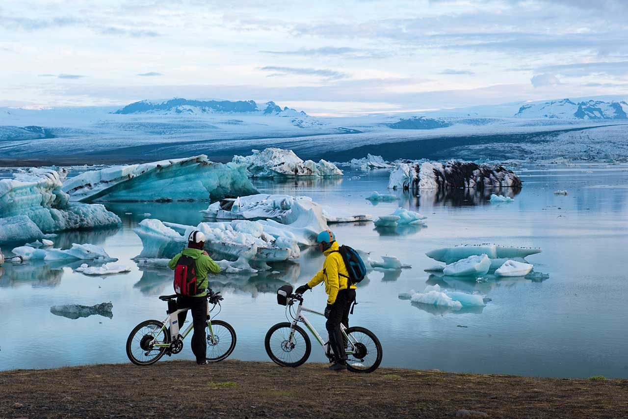 couple-riding-bikes-in-Iceland-with-glacers-blackground