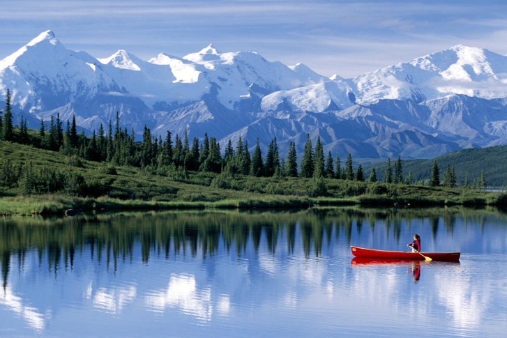 Prospect Creek, Alaska, lake on the background of beautiful mountain peaks with woman on a kayak, The Coldest Places in the World
