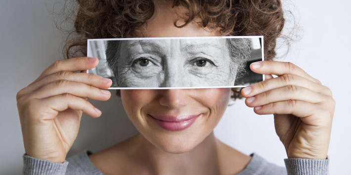Woman with photo of elderly woman's eyes on hers' , young and old woman