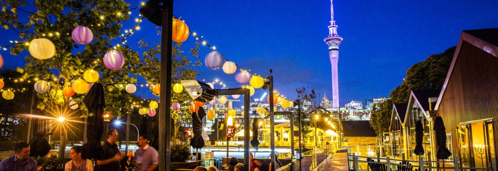 Auckland New Zealand by night lights people dining high tower