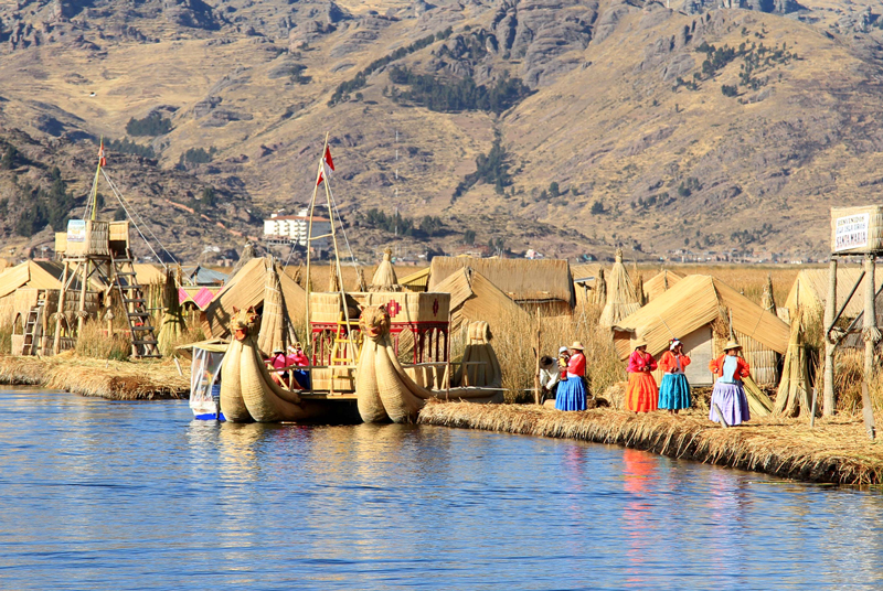 Islands-Uros-Lake-Titicaca,-Puno-city-Peru-artificial-island-made-of-cane-women-with-traditional-clothes