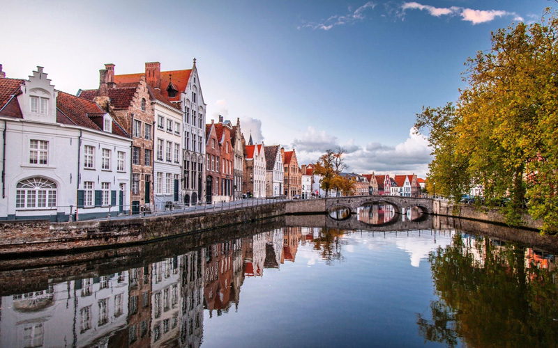 Fall-in-Belgium,-Bruges-top-fall-travel-destinations-beautiful-river-reflects-autumn-colors-perfect-picture-romantic-town-old-buildings