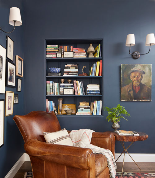 cozy reading chair country style reading nook on blue wall brown sofa wooden table portrait pictures on the wall