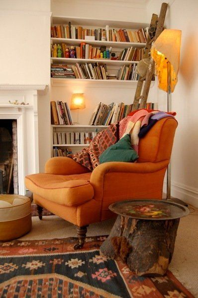 cozy reading chair orange fireplace wooden table colorful carpet white nook