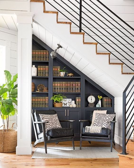cozy reading nook under tha stairs with two chairs