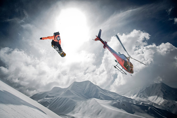 Snowboarder-jumping-with-helicopter-on-background-ski-movie-ski-resorts-holidays