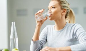 Woman-drinking-cup-of-water-limes-on-the-table