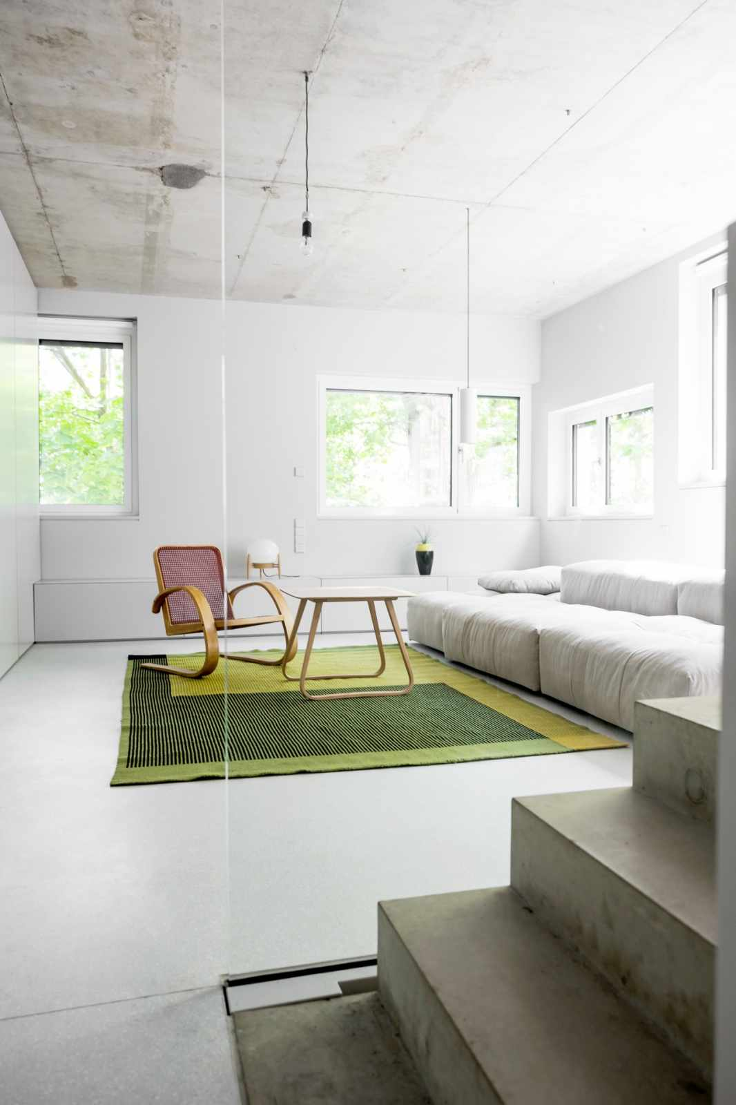 Minimalist Living Room with Green Rug and Grey Walls