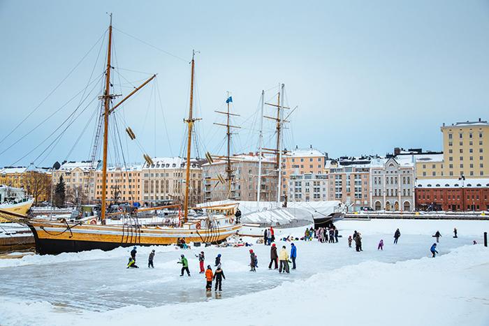 Children ice skating on frozen water in Helsinki port