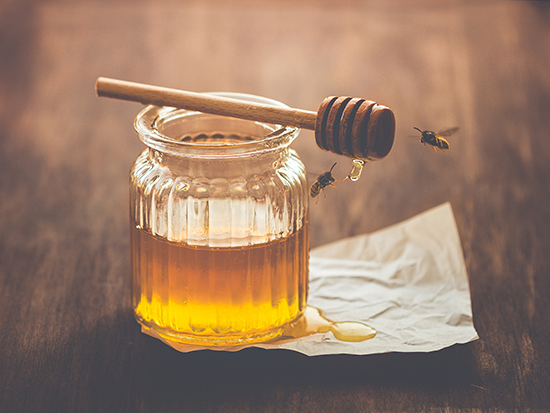 Honey in a jar with bees around