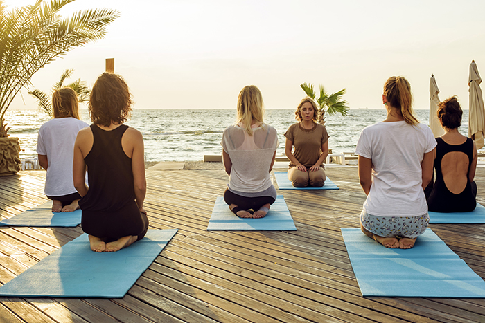 Group of people meditating on the beach