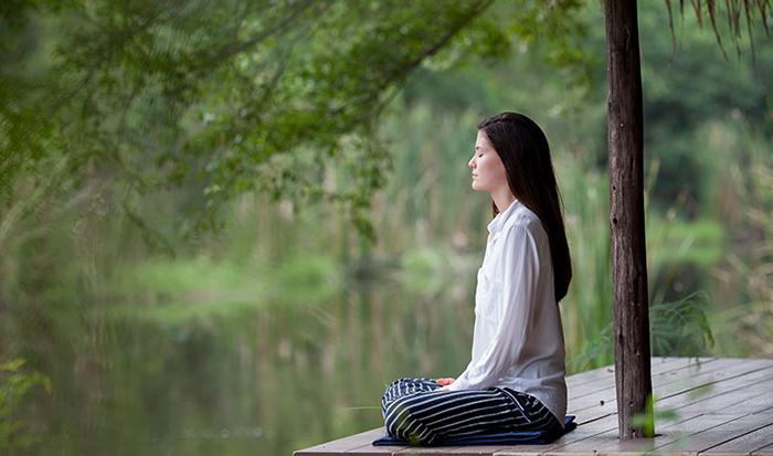 Woman having Silent Meditation near river