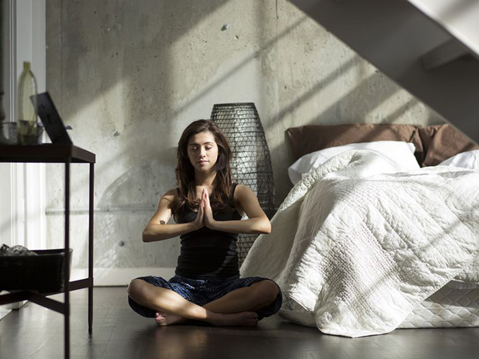 Woman meditating before sleep ritual