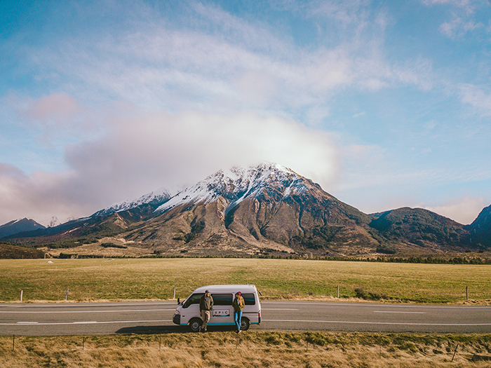 Couple with small bus having a break on south island road trip