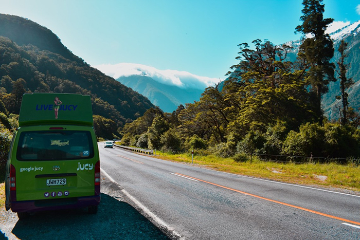 Green small bus travelling on South Island road trip
