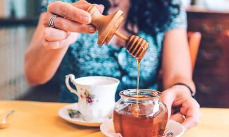 Woman puts honey in her tea