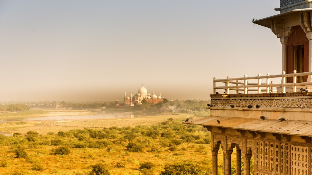 View on a meadow and Taj Mahal in India