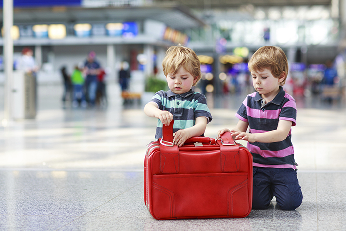 Two kids with red luggage on the airport