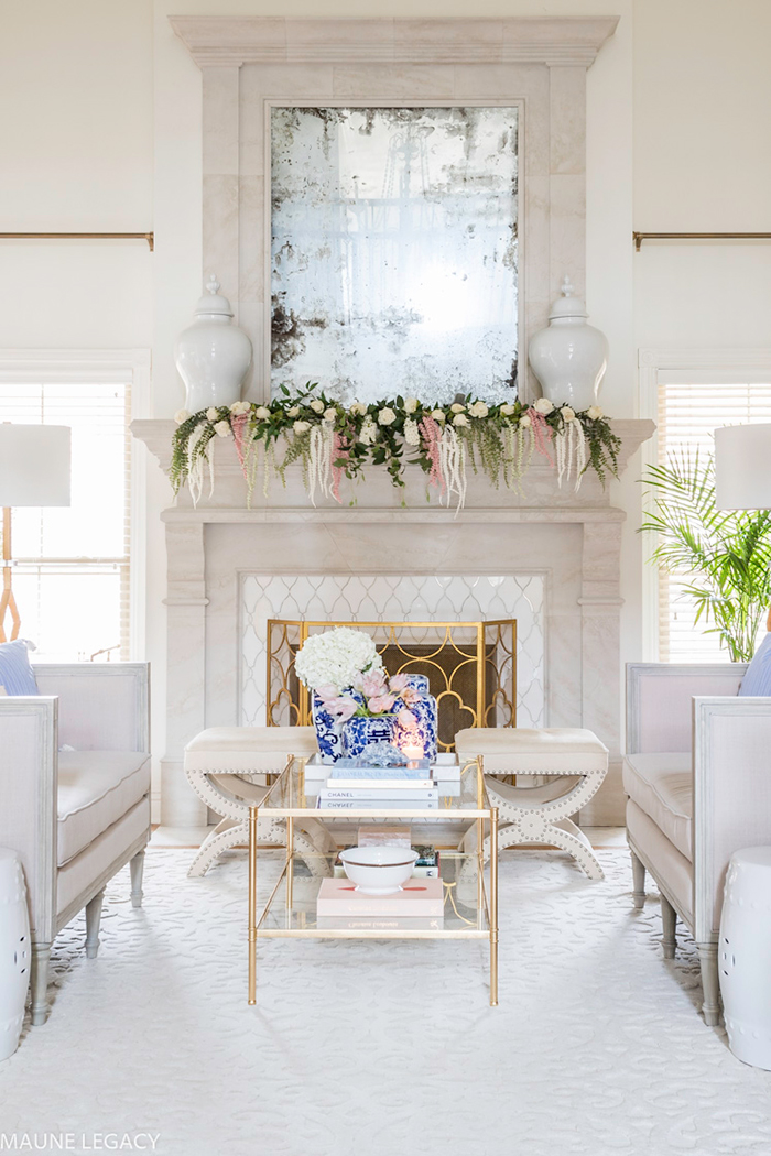 White living room with flower decor on fireplace