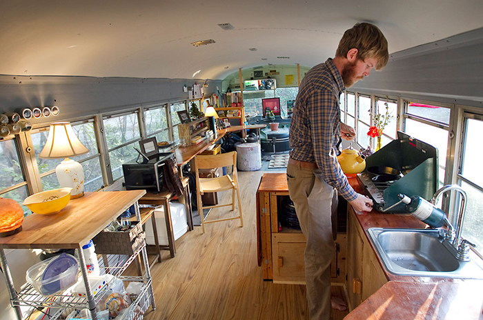 Man cooking in tiny house on wheels