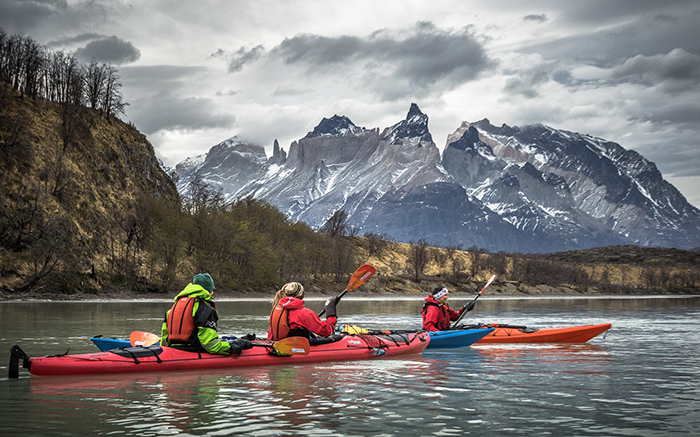 People kayaking in Torres del Paine National Park with mountains as a background