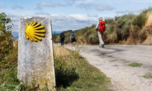 Pilgrims and a waymark showing the way