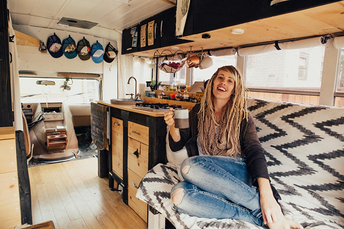 Girl drinking coffee in a small house on wheels