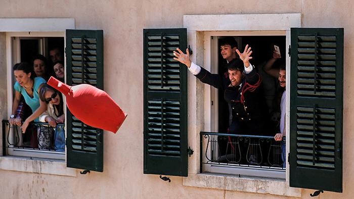 Man throwing large red pot from window in Corfu Greece Celebrating Easter
