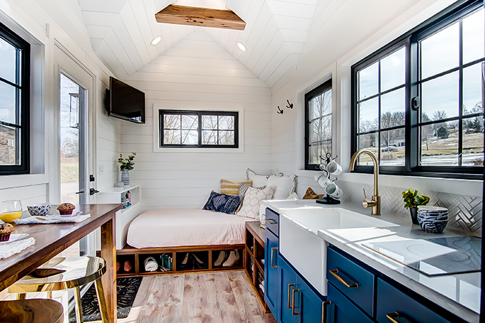 One floor tiny house with blue kitchen and wooden table