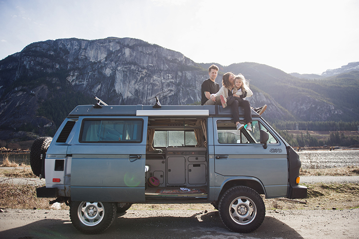 Family sitting on their house on wheels van