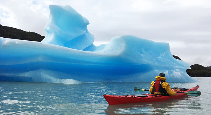Man kayaking near iceberg in Torres del Paine National Park, Chile