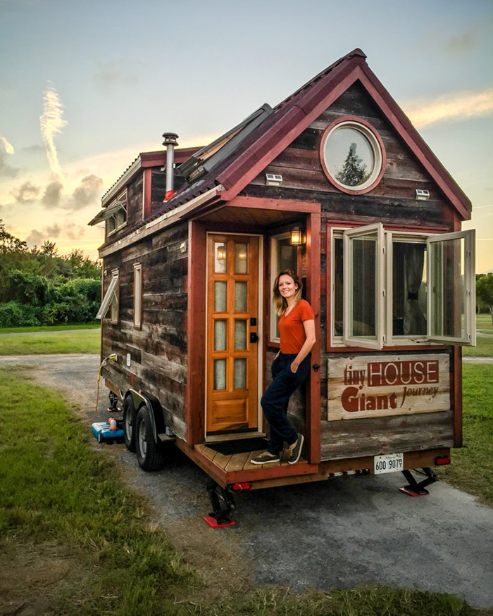 Small house on wheels with girl in front of it