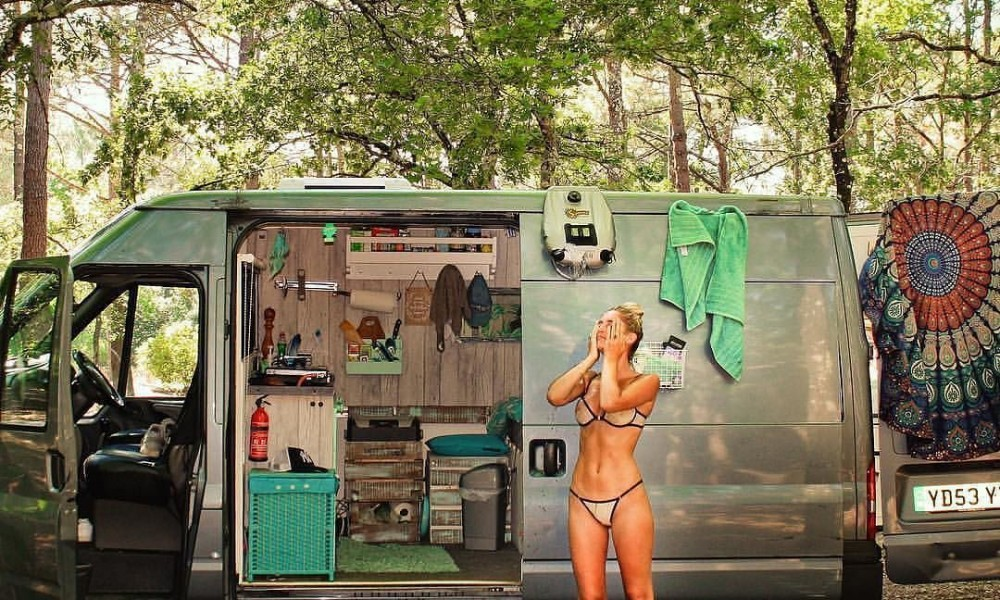Woman taking a shower in front of her tiny house on wheels