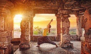Woman doing yoga on a sunset among ancient ruins in India
