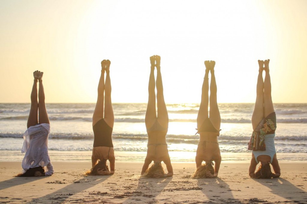 Women doing yoga during sunset at the beach