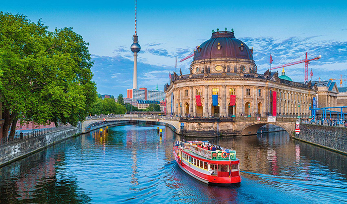 Tourists exploring Berlin on a boat with view on historical buildings