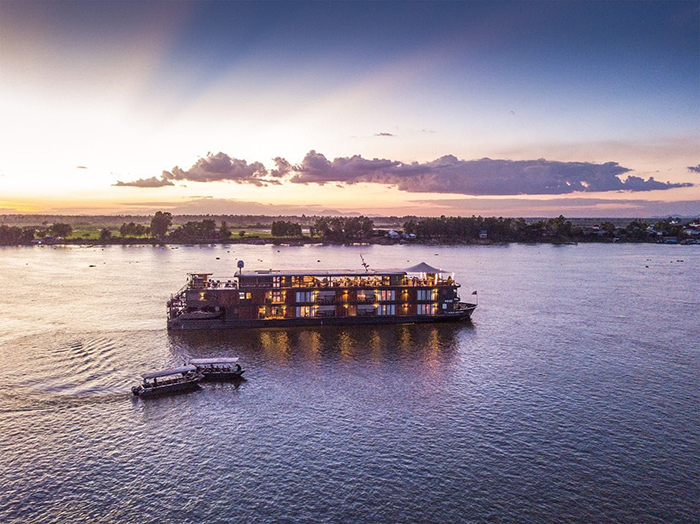 Floating hotel in Vietnam on a sunset and two small guest boats next to it