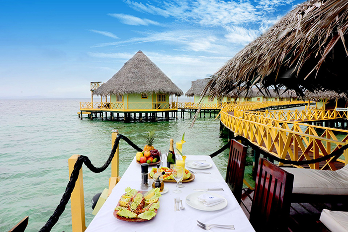 Eco-friendly floating hotel with a nice table decor full with tropical fruits and champagne